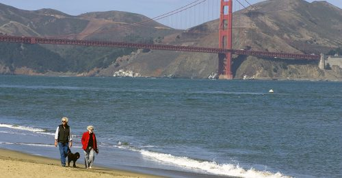 Chrissy- couple walking dog on beach with gg bridge in background